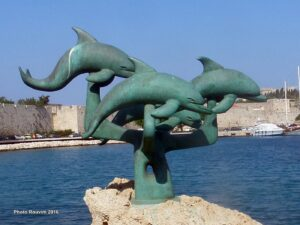 Three Dolphins are jumbing in the sea. Sculpture at the harbor in Rhodes